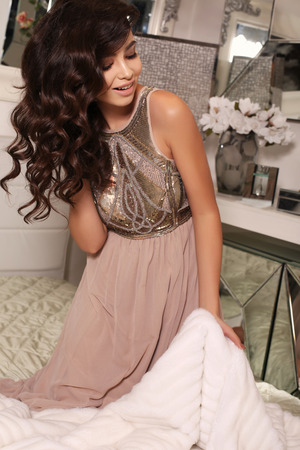 sensual girl: fashion interior photo of beautiful woman with dark curly hair and evening makeup,wears elegant dress