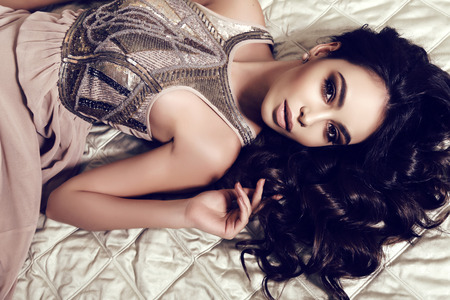 woman lying: fashion interior photo of beautiful woman with dark curly hair and evening makeup,wears elegant dress,lying on bed Stock Photo