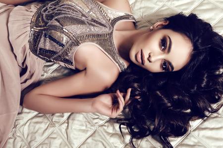 mujer elegante: moda foto interior de mujer hermosa con el pelo oscuro y rizado y maquillaje de noche, viste elegante vestido, acostado en la cama