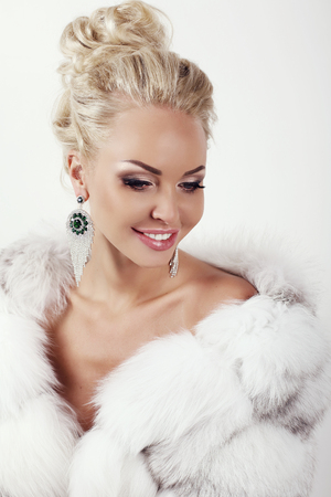 white coat: fashion studio photo of gorgeous sexy woman with long blond hair wears luxurios fur coat and bijou