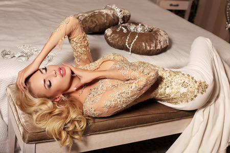 sexy bride: fashion interior photo of gorlgeous sexy woman with long blond hair wears luxurios lace wedding dress and bijou, posing in bedroom