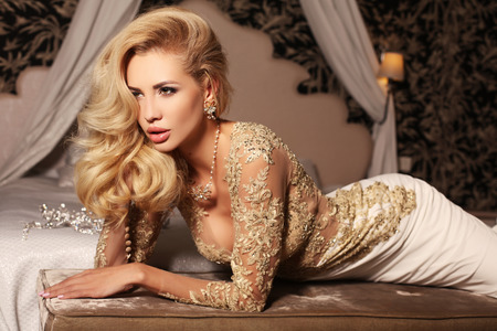 fashion girl style: fashion interior photo of gorlgeous sexy woman with long blond hair wears luxurios lace wedding dress,posing in bedroom