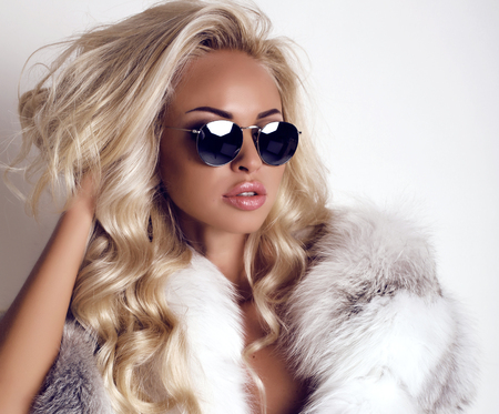 fashion studio photo of gorgeous woman with long blond hair wears luxurios fur coat and sunglasses
