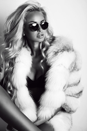 sexy photo: fashion black and white photo of gorgeous sexy woman with long blond hair wears luxurios fur coat and sunglasses