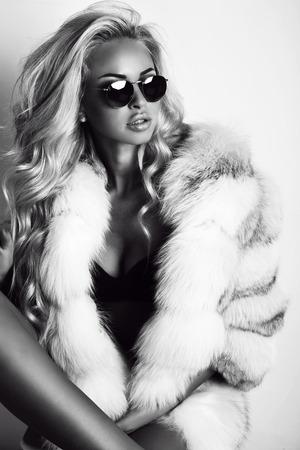 mode zwart-wit foto van prachtige sexy vrouw met lang blond haar draagt luxurios bontjas en een zonnebril