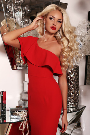 fashion interior photo of gorgeous sexy woman with long blond hair wears luxurious red dress and bijou