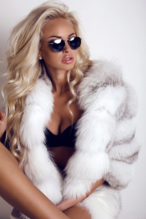 fashion studio foto van prachtige sexy vrouw met lang blond haar draagt luxurios bontjas en zonnebrillen