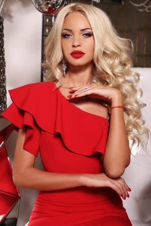 Foto di moda all'interno della splendida donna sexy con lunghi capelli biondi indossa lussuoso abito rosso e bijou