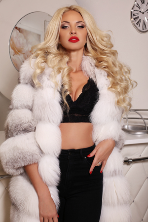 fashion interior photo of gorgeous sexy woman with long blond hair wears luxurious white fur coat and bijou