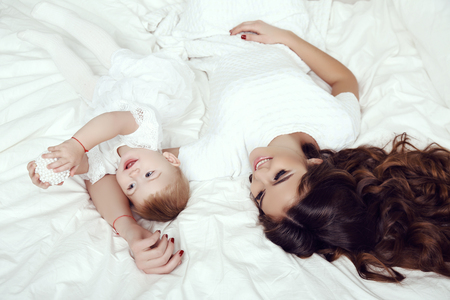 cozy: family photo of gorgeous woman with long dark hair wears elegant white dress posing with her little cute daughter in cozy room
