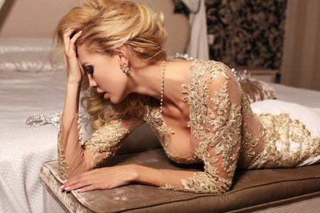 wedding dress: fashion interior photo of gorlgeous sexy woman with long blond hair wears luxurios lace wedding dress and bijou, posing in bedroom
