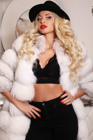 fur: fashion interior photo of gorgeous sexy woman with long blond hair wears luxurious white fur coat and black hat