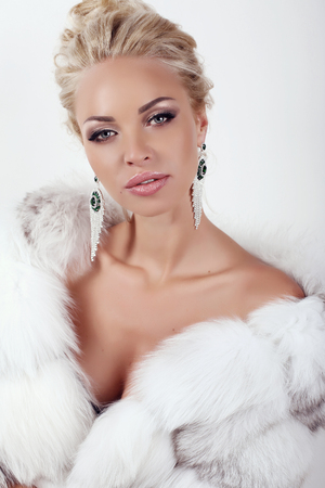 Mode Studio-Foto von wunderschönen sexy Frau mit langen blonden Haaren trägt Luxus Pelzmantel und Bijou