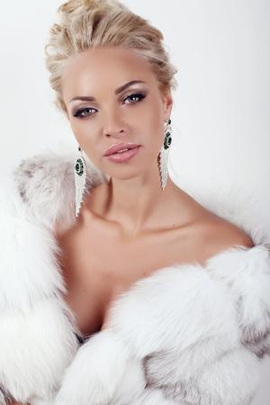 bata blanca: foto de estudio de moda de la mujer atractiva hermosa con el pelo rubio largo que desgasta la capa lujosas pieles y bijou