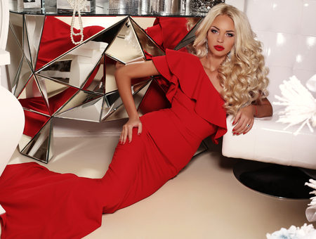 glamour hair: fashion interior photo of gorgeous sexy woman with long blond hair wears luxurious red dress and bijou