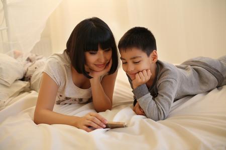 mama e hijo: tierna foto de familia de la madre hermosa con el pelo corto y oscuro y su pequeño hijo, que se divierten en el hogar acogedor, mirando película juntos