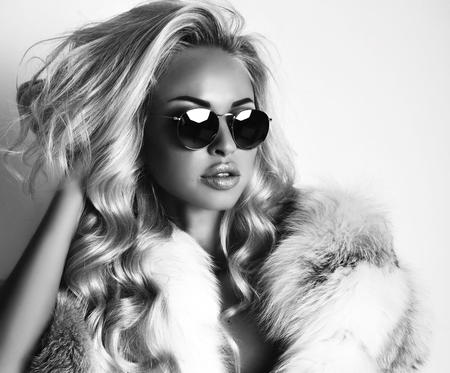 fashion studio black and white photo of gorgeous sexy woman with long blond hair wears luxurios fur coat and sunglasses