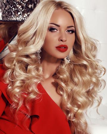 긴 금발 머리와 화려한 섹시 한 여자의 패션 인테리어 사진 고급스러운 빨간 드레스와 장식품을 착용 스톡 콘텐츠