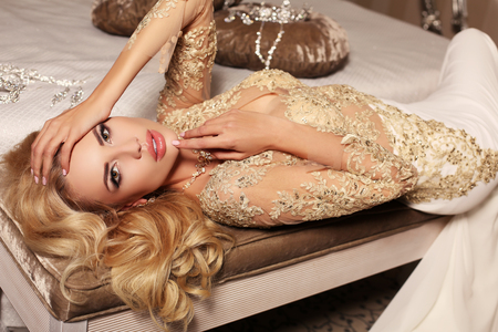fashion interior photo of gorlgeous sexy woman with long blond hair wears luxurios lace wedding dress and bijou, posing in bedroom