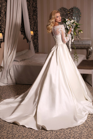 glowing skin: fashion studio photo of gorgeous bride with blond hair, in luxurious wedding dress with bijou, holding bouquet of flowers