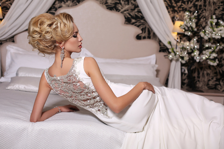 fashion studio photo of gorgeous bride with blond hair, in luxurious wedding dress with bijou, lying on bed