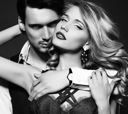 beauty model: black and white fashion studio photo of beautiful couple, wears elegant clothes, embracing each other