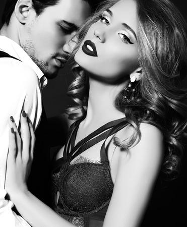zwart en wit mode studio foto van mooie paar, draagt elegante kleren, omhelzen elkaar