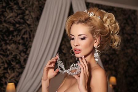 bijou: fashion studio photo of gorgeous bride with blond hair, in luxurious wedding dress with bijou and mask
