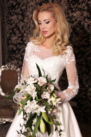 bijou: fashion studio photo of gorgeous bride with blond hair, in luxurious wedding dress with bijou, holding bouquet of flowers