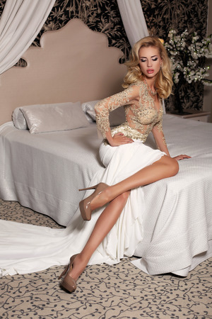 fashion studio photo of gorgeous bride with blond hair, in luxurious wedding dress with bijou, sitting on bed Stock Photo