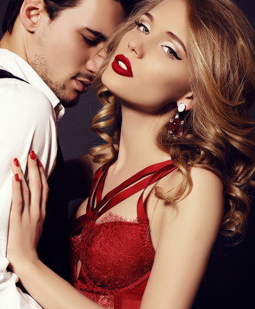 fashion studio photo of beautiful impassioned couple, wears elegant clothes, embracing each other