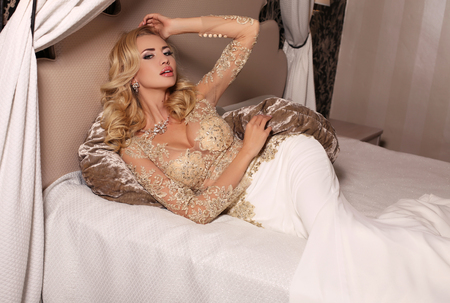 wedding dress: fashion studio photo of gorgeous bride with blond hair, in luxurious wedding dress with bijou, lying in bed