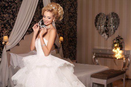 sexy bride: fashion studio photo of gorgeous bride with blond hair, in luxurious wedding dress with bijou and mask