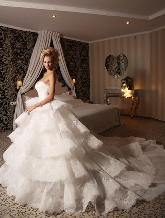sexy female: fashion studio photo of gorgeous bride with blond hair, in luxurious wedding dress with bijou, posing in elegant bedroom