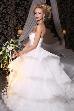 bijou: fashion studio photo of gorgeous bride with blond hair, in luxurious wedding dress with bijou, holding flowers bouquet