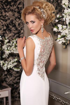 studio fotografico di moda della splendida sposa con i capelli biondi, in lussuoso abito da sposa con bijou, che presentano in sala decorata