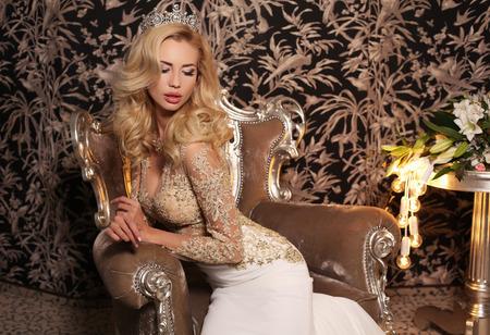 bijou: fashion studio photo of gorgeous bride with blond hair, in luxurious wedding dress with bijou, sitting on chair Stock Photo