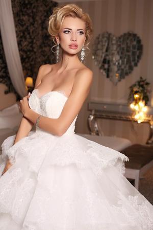 fashion studio photo of gorgeous bride with blond hair, in luxurious wedding dress with bijou