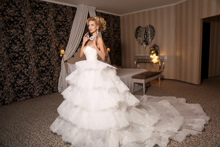 fashion studio photo of gorgeous bride with blond hair, in luxurious wedding dress with bijou posing in room