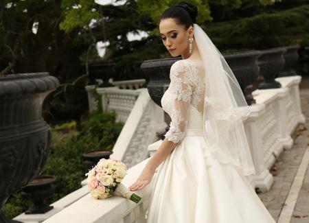 Foto di moda all'aperto della splendida sposa con i capelli scuri indossa abito da sposa elegante, in posa nel parco