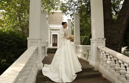 bride dress: fashion outdoor photo of gorgeous bride with dark hair wears elegant wedding dress, posing in park on stairs