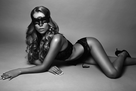 black woman lingerie: fashion black and white studio photo of beautiful sexy woman with long blond curly hair wears elegant lingerie and lace mask on face