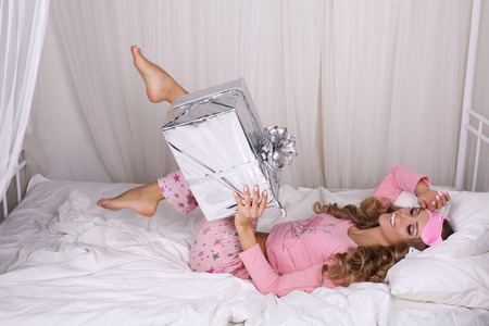 sleeping mask: fashion interior photo of beautiful sexy woman with long blond curly hair wears pajama and sleeping mask posing in bedroom with present Stock Photo
