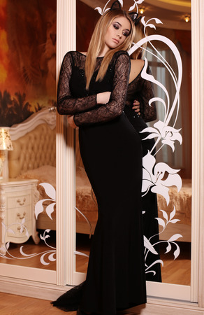 glamour hair: fashion interior photo of beautiful glamour woman with blond hair in elegant black dress  posing in bedroom Stock Photo