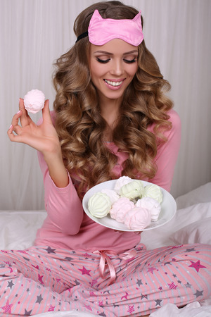 sleeping mask: fashion interior photo of beautiful sexy woman with long blond curly hair wears pajama and sleeping mask, eating sweets Stock Photo
