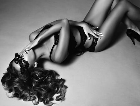 fashion black and white studio photo of beautiful sexy woman with long blond curly hair wears elegant lingerie and lace mask on face