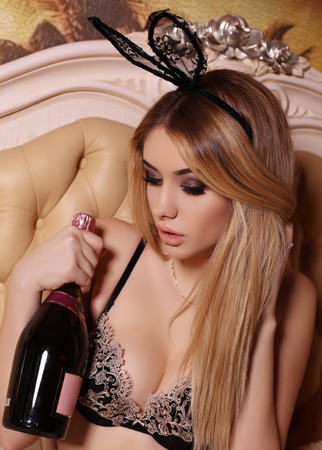mode photo intérieur de belle femme glamour avec des cheveux blonds en lingerie et lapin oreilles élégant bandeau, posant dans la chambre, tenant une bouteille de vin à la main