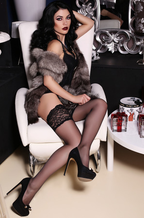 fashion interior photo of beautiful sensual woman with dark hair wears black lingerie, pantyhose and fur coat