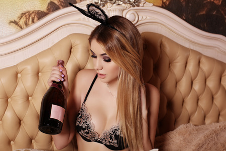bottle of wine: fashion interior photo of beautiful glamour woman with blond hair in elegant lingerie and bunny ears headband, posing in bedroom,holding bottle of wine in hand
