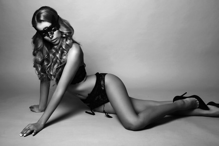 sexy black woman: fashion black and white studio photo of beautiful sexy woman with long blond curly hair wears elegant lingerie and lace mask on face